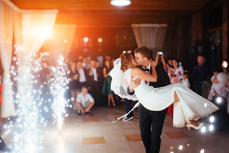 a imagem mostra uma noiva e um noivo dançando felizes. O noivo está com a noiva no colo. Música para casamento 2021