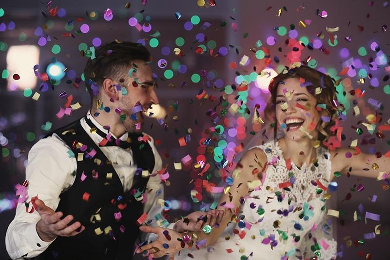 A imagem mostra um noiva e uma noiva sorrindo e papéis coloridos caindo. Música para casamento 2021