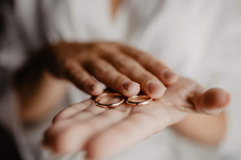 a imagem mostra uma mão feminina segurando duas alianças de casamento