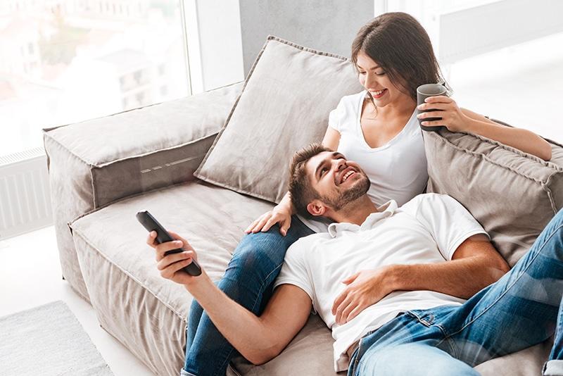 uma mulher sentada no sofá e um homen deitado no colo dela segurando um controle