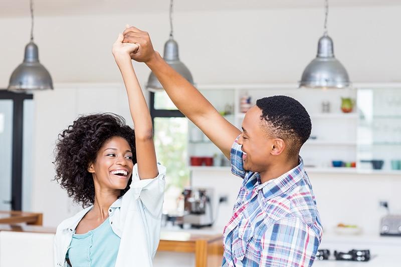 um homem e uma mulher dançando felizes na cozinha