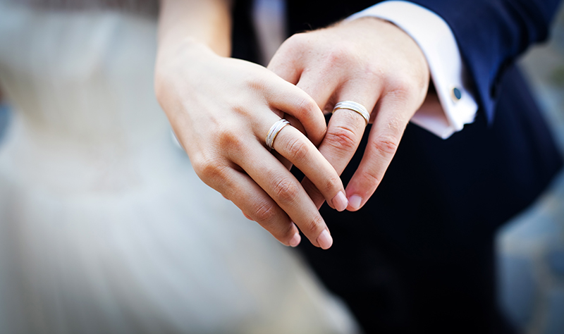 uma mão feminina e uma mão masculina mostrando as alianças de casamento
