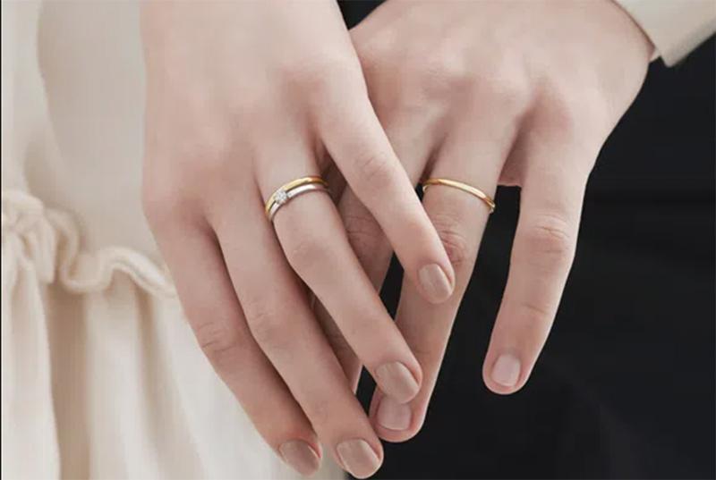 um par de mãos feminina e masculina usando alianças de casamento