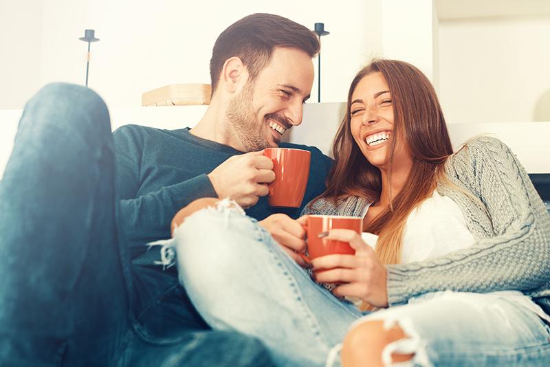 casal jovem de homem e mulher sorrindo e segurando uma cancea vermelha