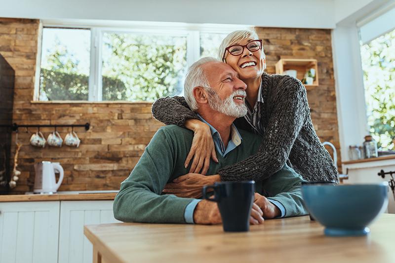 homem e mulher mais velhos, abraçados e sorrindo