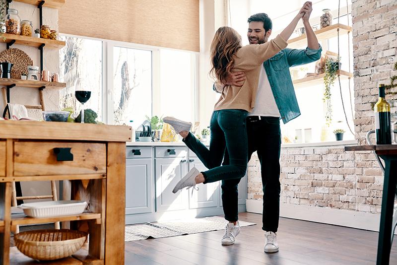 Casal de homem e mulher jovens, dançando na cozinha