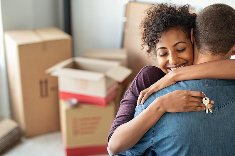 casal jovem se abraçando com caixas ao fundo e segurando uma chave