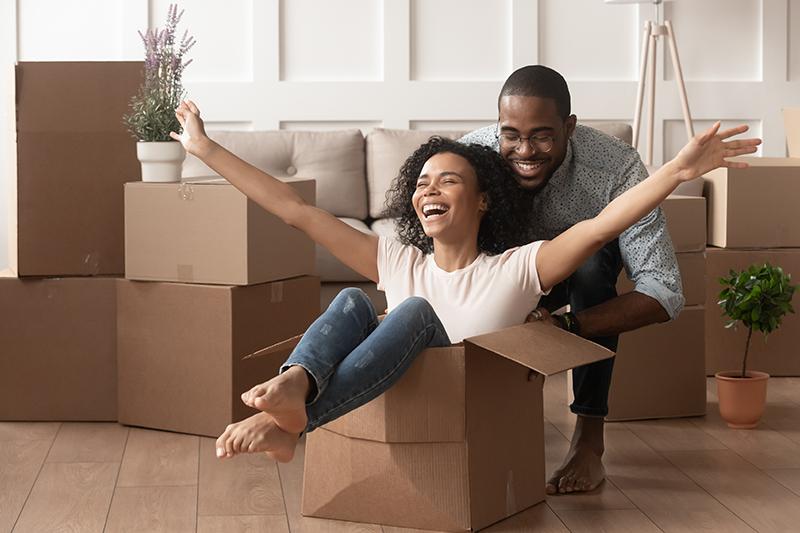 casal de homem e mulher negros felizes e sorrindo. Ele está empurrando ela dentro de uma caixa