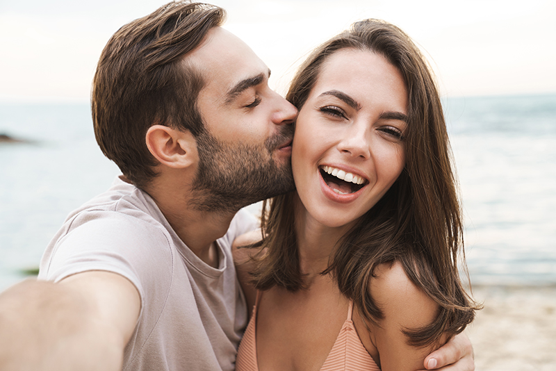 Image of young happy man kissing and hugging beautiful woman while taking selfie photo on sunny beach