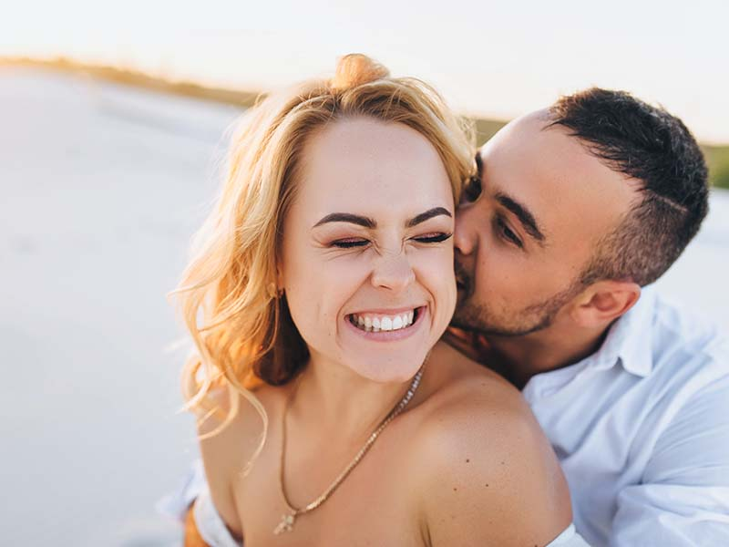 A bearded man and a blond woman hugging against the background of white sand. Portrait of emotional people at sunset. Love in the desert newlyweds. The love story of merry lovers young.Kiss and smile.